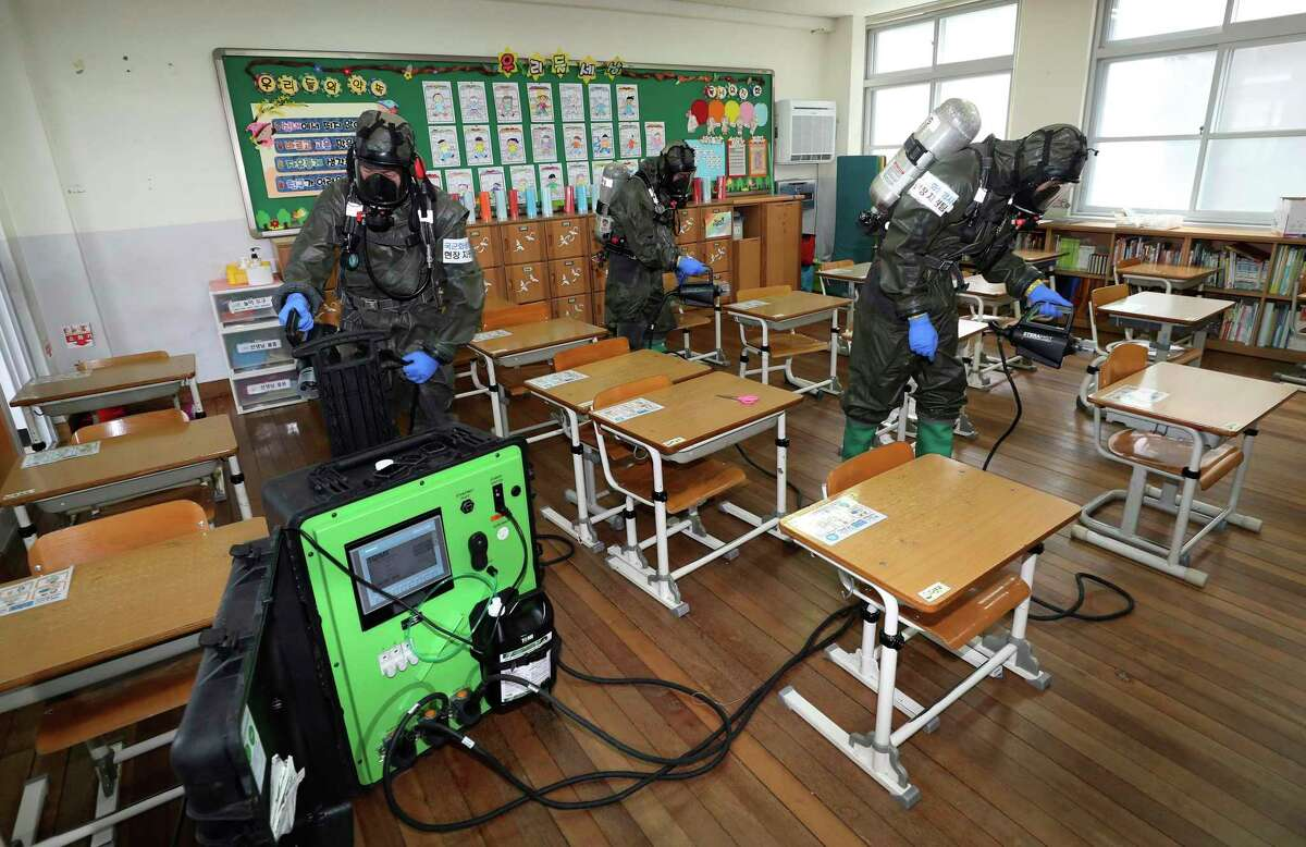 South Korean army soldiers spray disinfectant to help reduce the spread of the new coronavirus in a class July 2 at Cheondong Elementary School in Daejeon, South Korea. New research out of South Korea suggested children between the ages of 10 and 19 could spread the novel coronavirus at rates similar to adults, though the study had a relatively small sample size of about 124 infected children and teenagers.