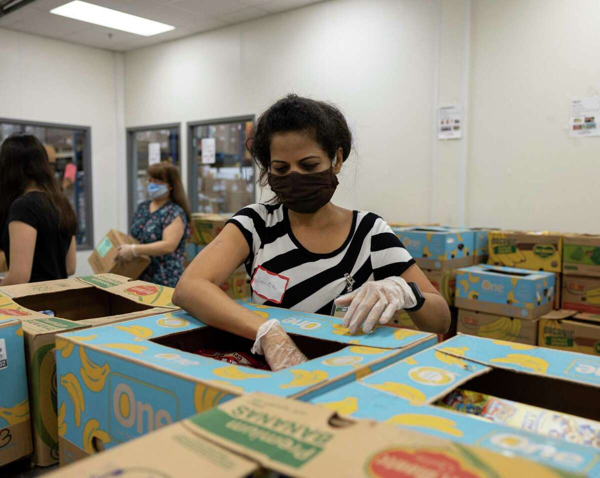 Savita sorts through a box of assembled food at the Montgomery County Food Bank in Conroe, Tuesday, July 21, 2020. The food bank is in need of volunteers after the National Guard was called back to their posts.