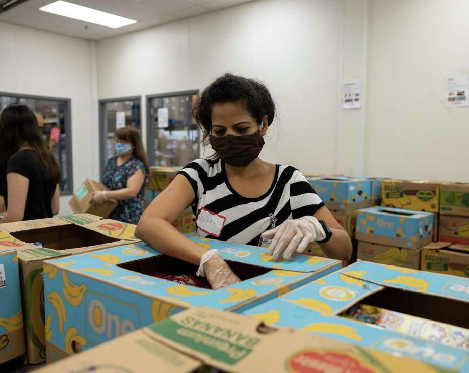 Savita sorts through a box of assembled food at the Montgomery County Food Bank in Conroe, Tuesday, July 21, 2020. The food bank is in need of volunteers after the National Guard was called back to their posts. Photo: Gustavo Huerta, Houston Chronicle / Staff Photographer / Houston Chronicle © 2020