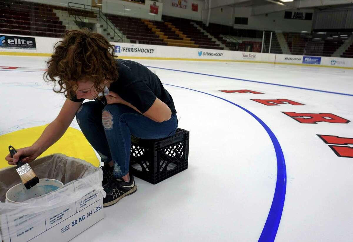 Hailey Dard meticulously fills in Ferris State's logo with paint at Ewigleben Arena. (Pioneer photos/Joe Judd)