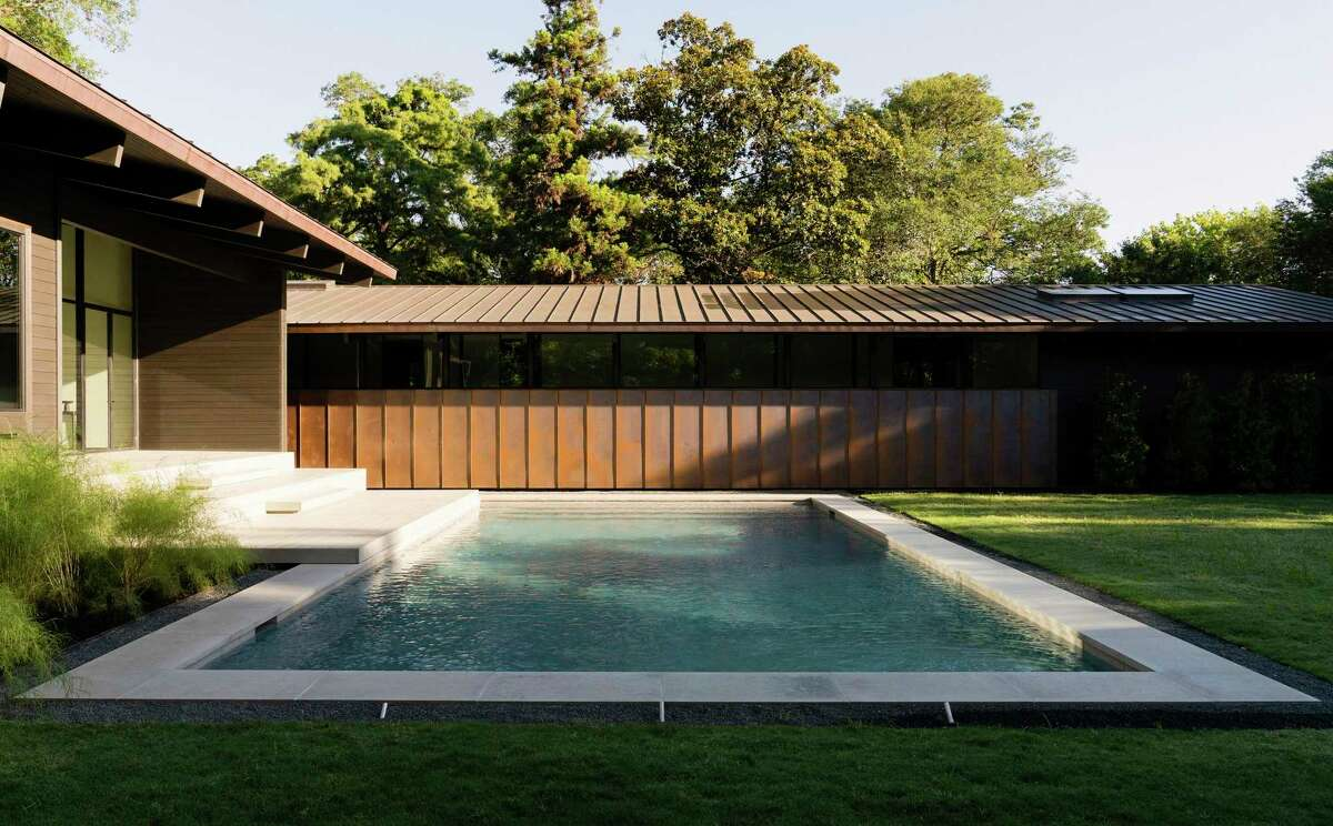The home has a copper roof, and one side of the L-shaped home has panels of copper up a partial wall that you see from the backyard.