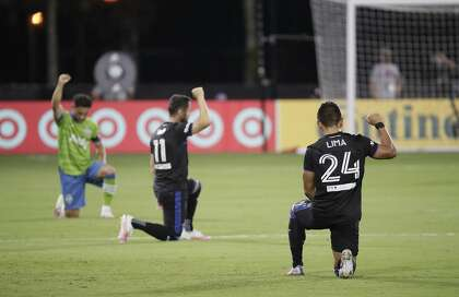 Players from both teams kneel and raise their fists in the air in solidarity to the Black Lives Matter movement before the start of an MLS soccer match between the San Jose Earthquakes and the Seattle Sounders, Friday, July 10, 2020, in Kissimmee, Fla. (AP Photo/John Raoux)