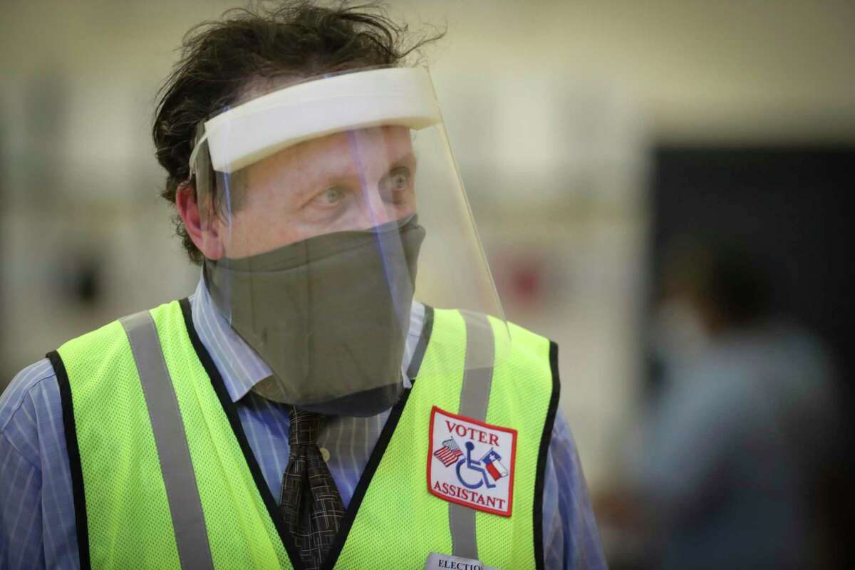 Voter essistant Marvin Hass, wearing a face mask and shield, aids voters at the Metropolitan Multi-Services Center during a runoff election, Tuesday, July 14, 2020, in Houston. (Steve Gonzales/Houston Chronicle via AP)