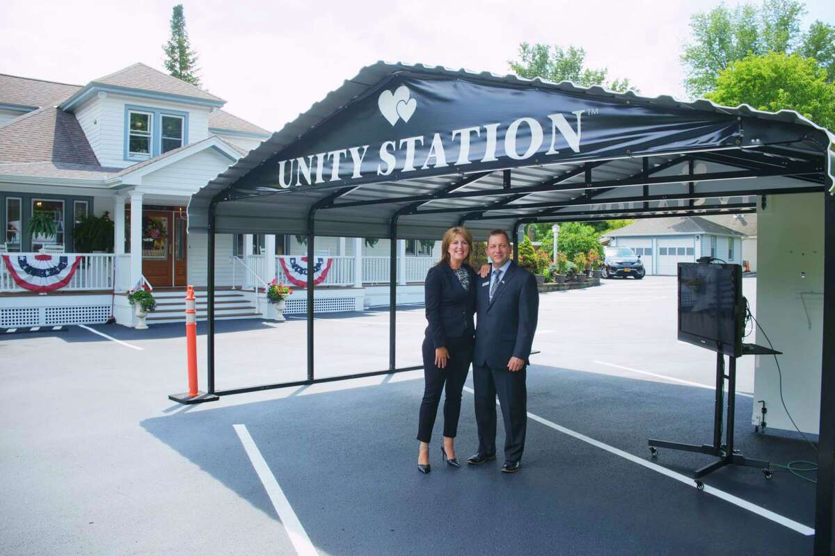Kathleen Sanvidge, left, owner of Townley and Wheeler Funeral Home, and her fiancé, Zoltan Prohaszka, who is the IT specialist at the funeral home, stand under the outside shelter on Thursday, July 23, 2020, in Ballston Lake, N.Y. The shelter, they call Unity Station, allows for people in their vehicles to virtually connect through a monitor to family members inside the funeral home. (Paul Buckowski/Times Union)
