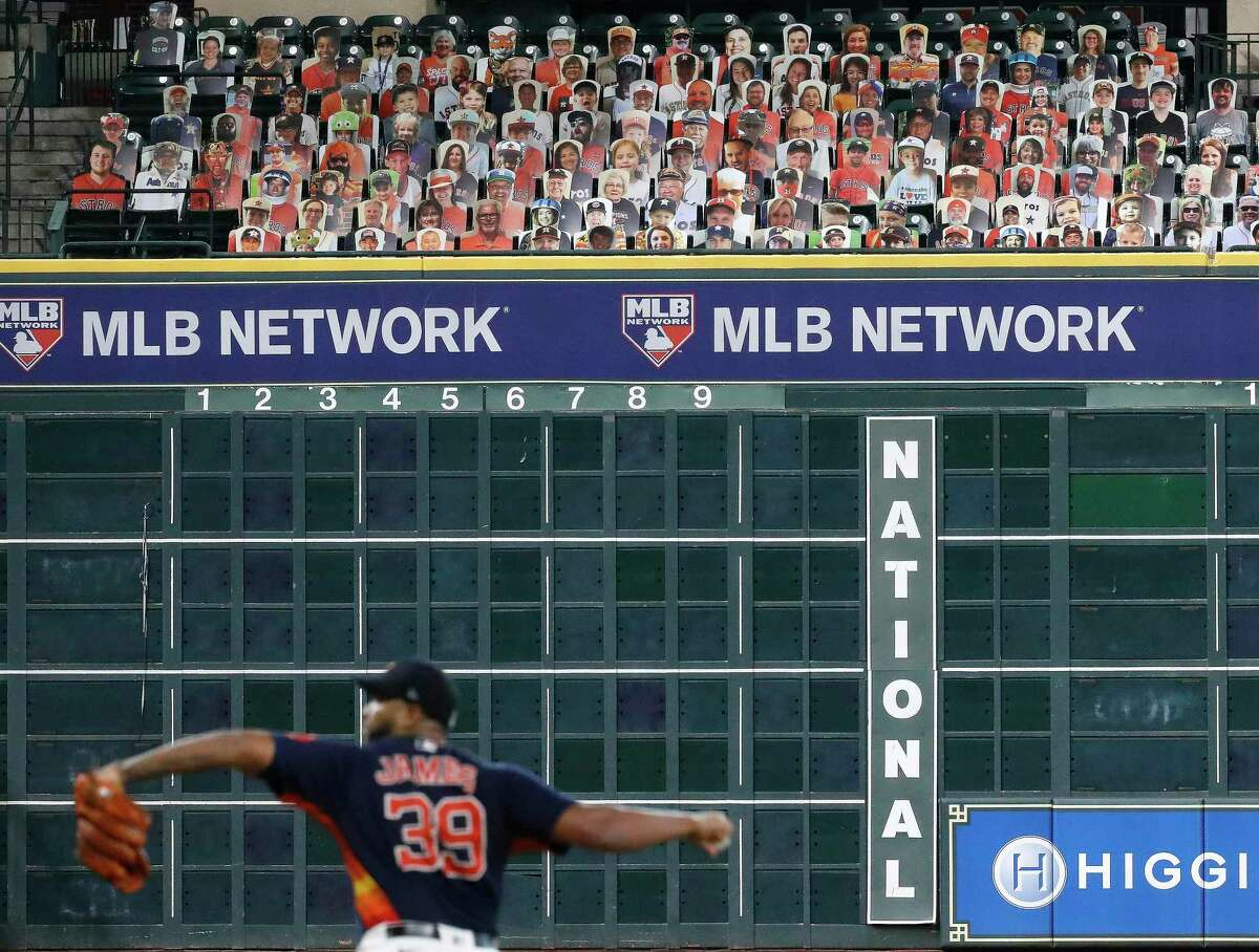 Houston Astros pitcher Josh James pitches with cardboard cutouts of fans in the Crawford Boxes behind him during an intrasquad game during the Astros summer camp at Minute Maid Park, Wednesday, July 22, 2020, in Houston.