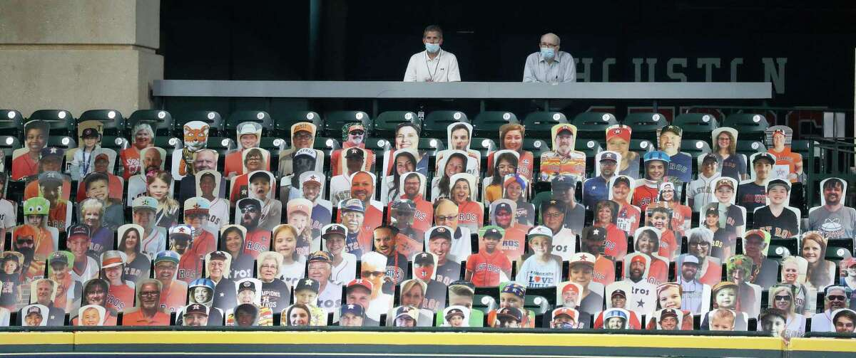 Two live men stand behind a section of cardboard cutouts of Astros fans in the Crawford Boxes during an intrasquad game during the Astros summer camp at Minute Maid Park, Wednesday, July 22, 2020, in Houston.