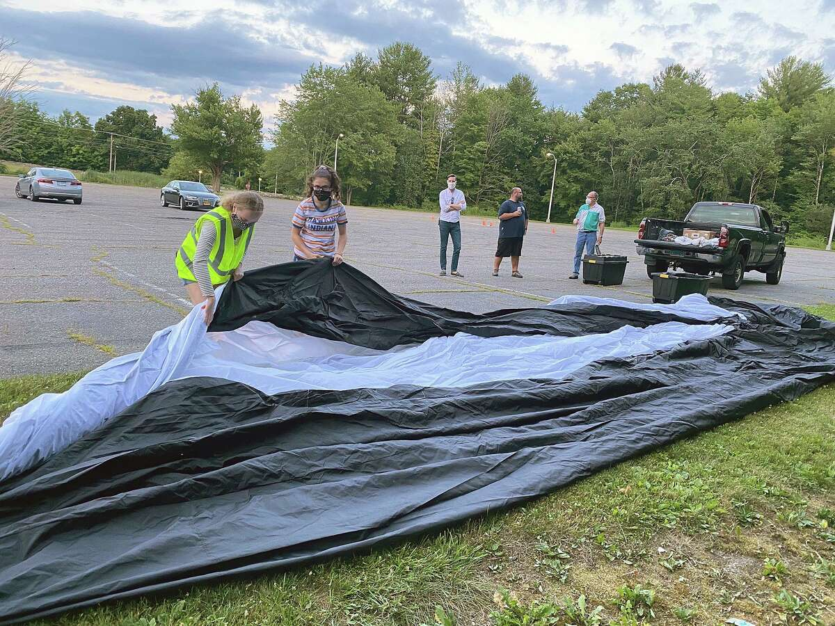 Torrington Library Teen Advisory Board members Maia Blauvelt, wearing safety vest, and Ellie Ercoli help unfold the inflatable 40-foot screen during a practice session Tuesday night in advance of opening night Saturday at the Torrington Drive-In at Five Points.