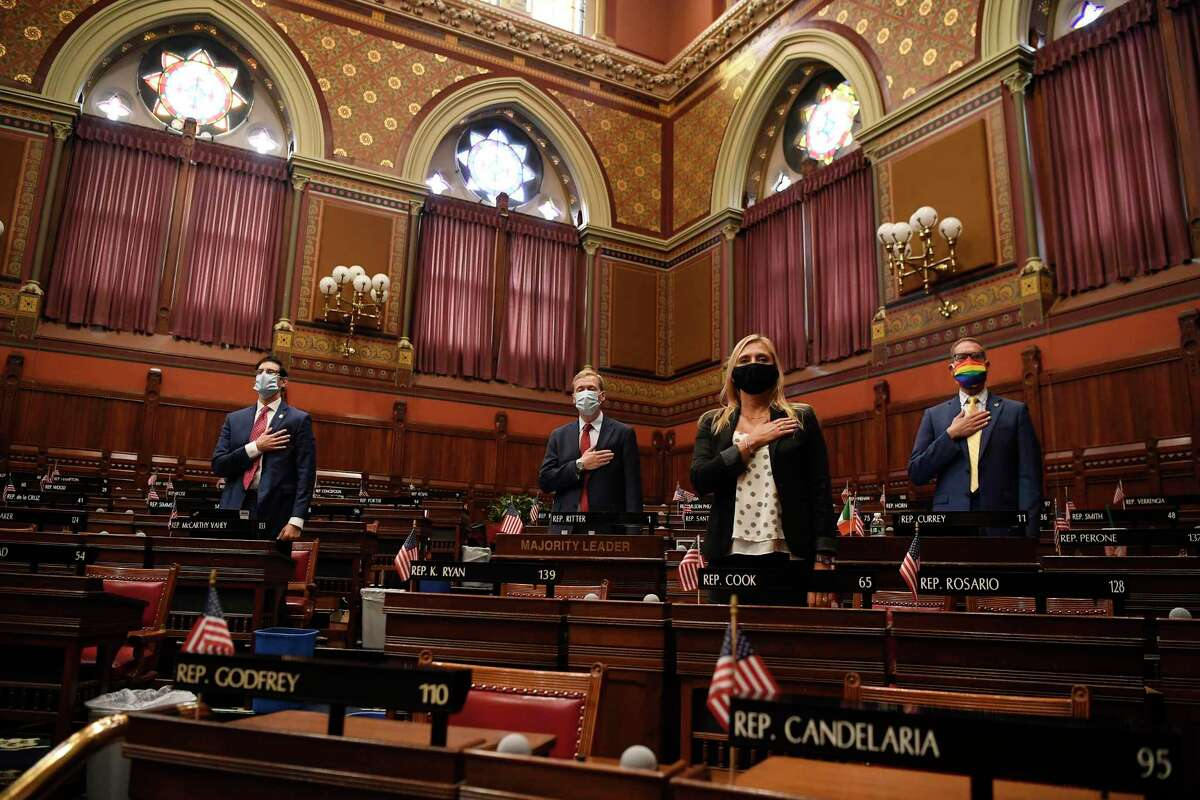 Connecticut House Majority Leader Matt Ritter, D-Hartford, second from left, stands with fellow Democrats in the House, as they stand for the Pledge of Allegiance during the start of a special session at the State Capitol, Thursday, July 23, 2020, in Hartford, Conn. (AP Photo/Jessica Hill)