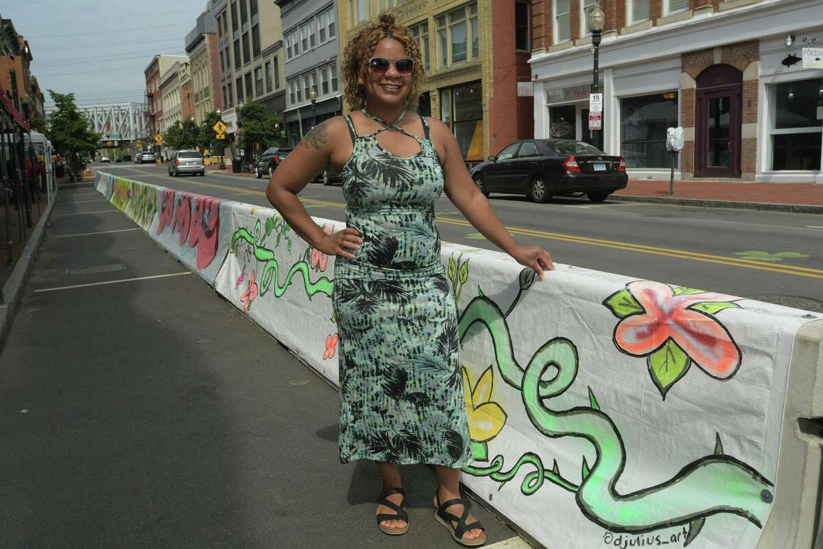 The Norwalk Arts Commission and local artists inclding Bridgeport resident Danielle Julius who painted murals on tarps that now cover concrete barriers on Washington Street meet for the official unveiling Thursday, July 23, 2020, in Norwalk, Conn. The barriers were installed to expand outdoor dining space for restaurants during the pandemic and artists painted murals in the theme of