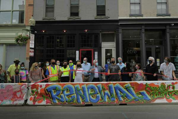 """Mayor Rilling meets with the Norwalk Arts Commission and local artists who painted murals on tarps that now cover concrete barriers on Washington Street Thursday, July 23, 2020, in Norwalk, Conn. The barriers were installed to expand outdoor dining space for restaurants during the pandemic and artists painted murals in the theme of """"renewal"""" for this new outdoor gallery curated by the Arts Commission."""