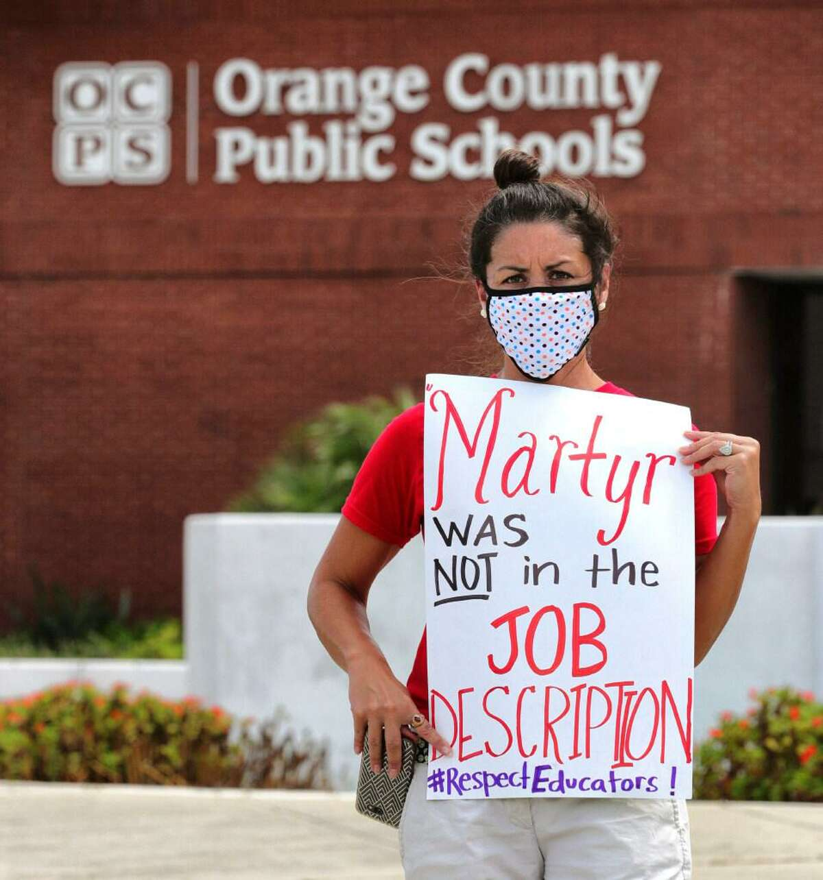 In this Tuesday, July 7, 2020 file photo, Rachel Bardes holds a sign in front of the Orange County Public Schools headquarters as teachers protest with a car parade around the administration center in downtown Orlando, Fla. As pressure mounts for teachers to return to their classrooms this fall, concerns about the pandemic are pushing many toward alternatives, including career changes, as some mobilize to delay school reopenings in areas hardest hit by the coronavirus.