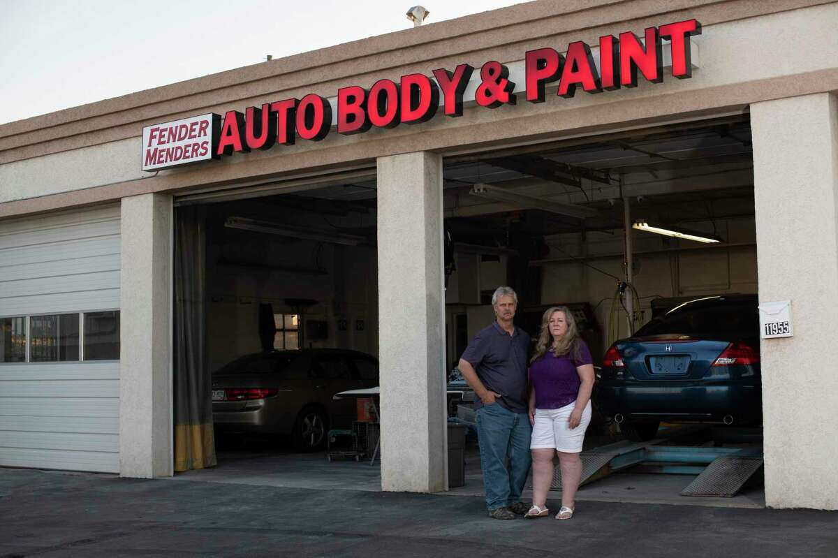 Scott and Tammy Nelson, co-owners of Fender Menders, an auto body shop, pose in front of their garage in Broomfield, Colo. The Nelsons accepted a PPP loan in April, which ran out at the end of June.