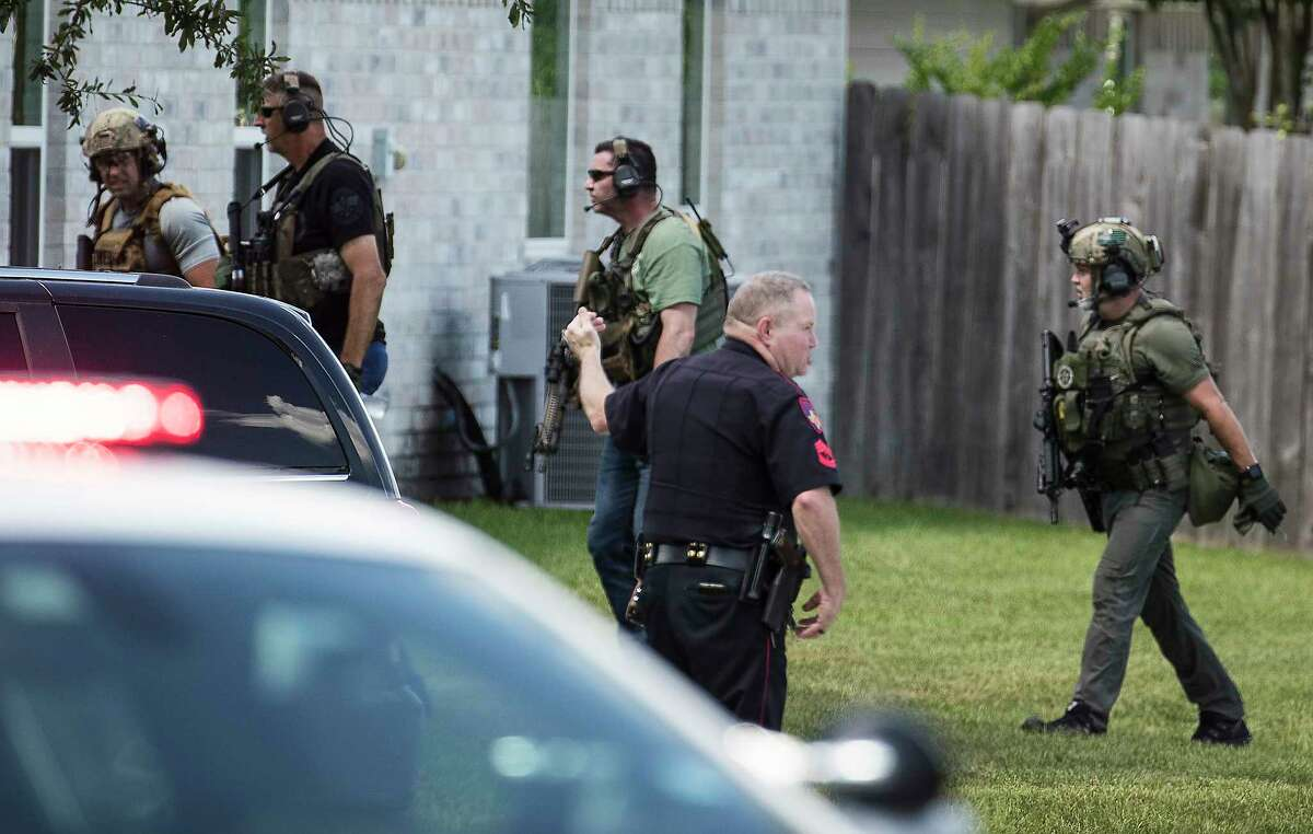 Law enforcement officers work the scene where a shooting suspect is holed up inside a house on Thursday, July 23, 2020 in Cypress. Harris County sheriff's deputies faced gunfire Thursday at a home where they had been searching for a Montgomery County murder suspect, authorities said. Multiple gunshots were fired at deputies from the home in the 15200 block of Vincennes Oak in the Cypress area, the sheriff's office said. Deputies had been at the home searching for Christopher Julian, 27, who is accused of gunning down a 29-year-old father inside a Magnolia home late Wednesday night.