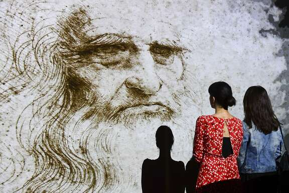 "People watch a hologram called ""Studio di uomo barbuto"" (study of bearded man) during the Leonardo da Vinci multimedia installation ""Leonardo Da Vinci 3D"" at the Fabbrica del Vapore (Steam Factory) in Milan, on May 29, 2019. - The exhibition taking place from May 30 to September 22, 2019, breaks through traditional art exhibition boundaries, challenging the laws of physics, time and space with lights, images, sounds and colors. 2019 marks the 500th anniversary of the death of the artist and inventor. (Photo by Miguel MEDINA / AFP) / RESTRICTED TO EDITORIAL USE - MANDATORY MENTION OF THE ARTIST UPON PUBLICATION - TO ILLUSTRATE THE EVENT AS SPECIFIED IN THE CAPTION        (Photo credit should read MIGUEL MEDINA/AFP via Getty Images)"