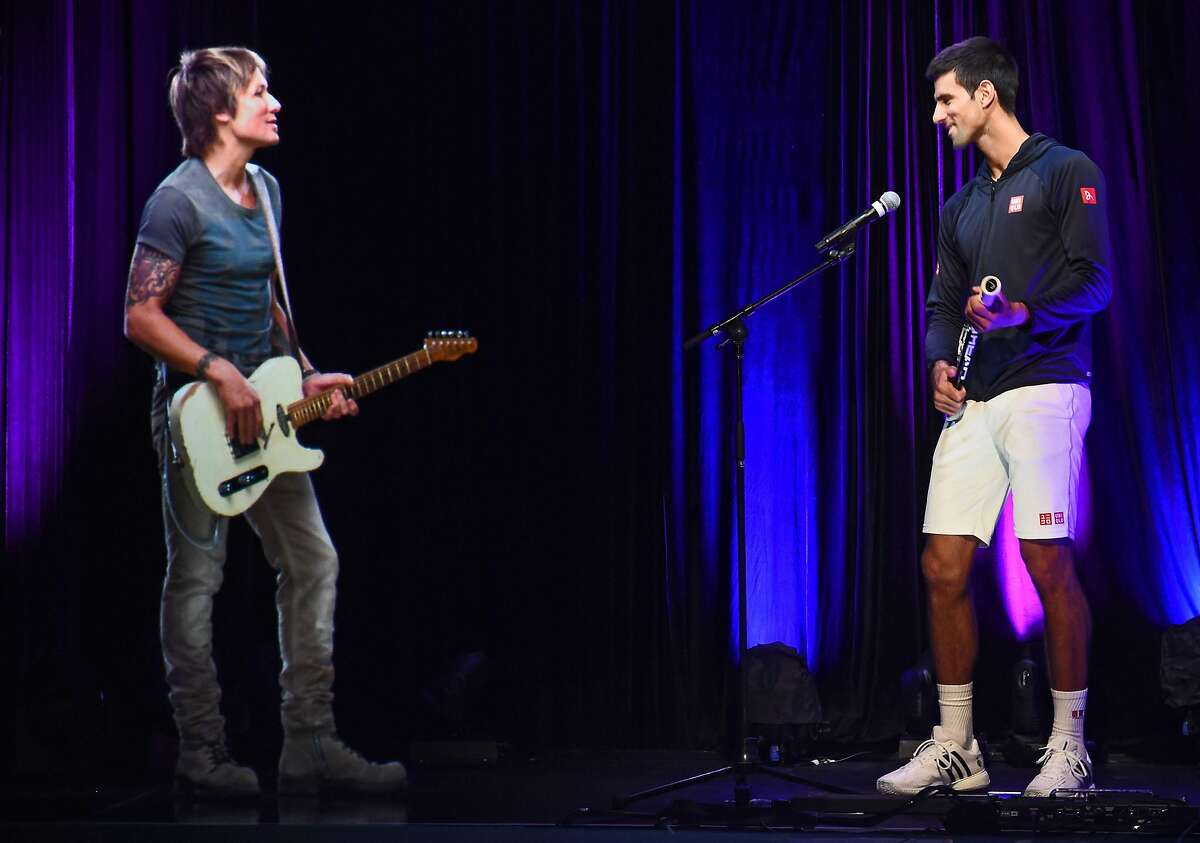 MELBOURNE, AUSTRALIA - JANUARY 25: Novak Djokovic plays guitar at the ANZ Jam Slam on Grand Slam Oval with a hologram of Aussie music star Keith Urban during the 2015 Australian Open at Melbourne Park on January 25, 2015 in Melbourne, Australia. ~~
