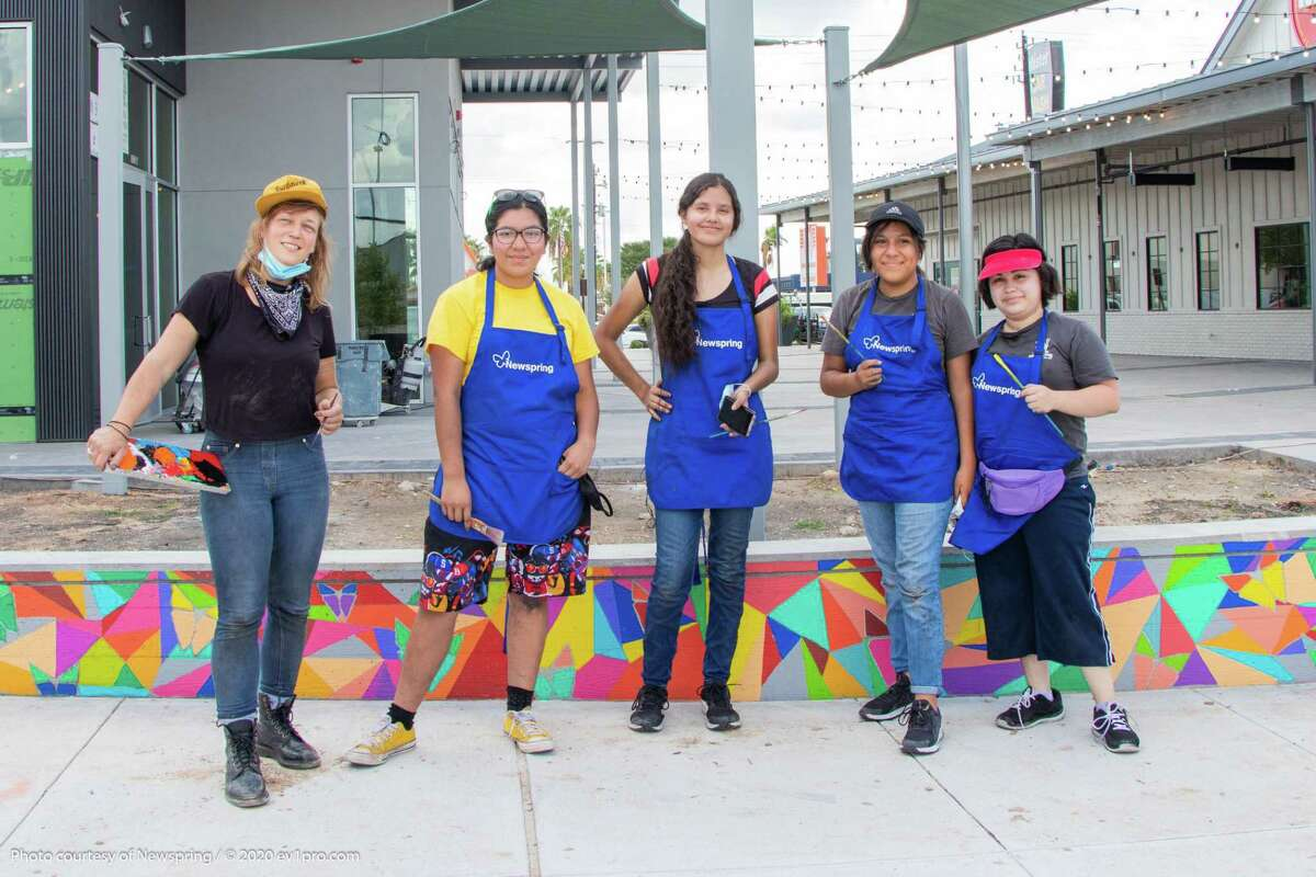 From left, artists Melissa Eason, Aileen Fuentes Martinez, Alisson Terreros, Selene Peralta, and Daniela Cruz stand in front of the mural that they painted on the seat wall at a new mixed-use project on the northwest corner of the intersection of Gessner Road and the Katy Freeway.