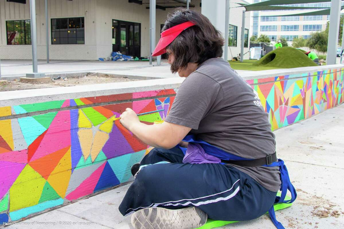 Daniela Cruz works on the mural on the seat wall at a new mixed-use project on the northwest corner of the intersection of Gessner Road and the Katy Freeway.