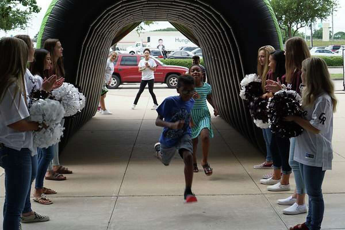Compassion Katy hopes to set up around 3,000 Katy Independent School District elementary students with backpacks and supplies for the new school year through its Operation Back 2 School drive-thru event. Some students pictured here are cheered on at the 2019 event.