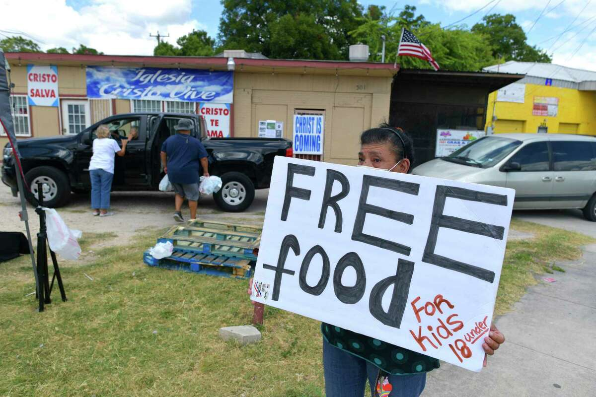 Francisca Walker holds a sign informing motorists and pedestrians about the food giveaway at Iglesia Cristo Vive, 301 Fredericksburg Road, on Thursday, July 23, 2020. The giveaway is hosted by Blessings of Hands Ministries and El Shaddai Ministries. The food is provided by Be A Champion. The giveaway is on Thursdays from 11 a.m. to about 1 p.m., or until the food runs out.