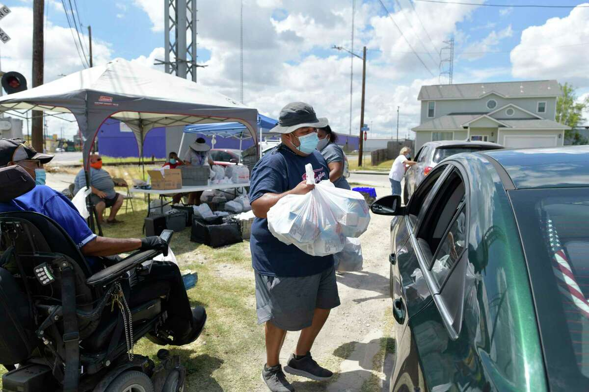 David Guerrero loads bags during a food giveaway at Iglesia Cristo Vive, 301 Fredericksburg Road, on Thursday, July 23, 2020. The giveaway is hosted by Blessings of Hands Ministries and El Shaddai Ministries. The food is provided by Be A Champion.
