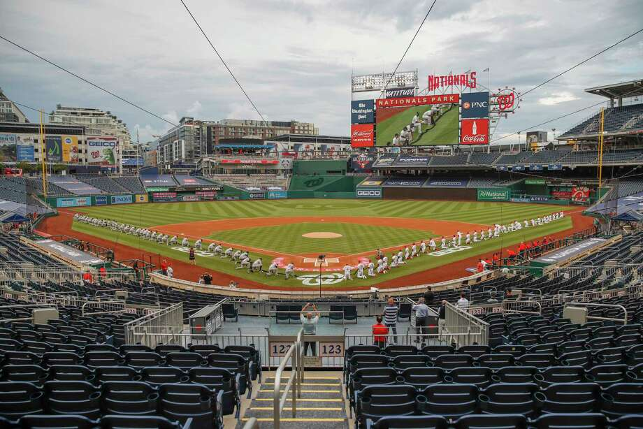 The New York Yankees and the Washington Nationals kneel while holding a black ribbon to honor Black Lives Matter before playing an opening day baseball game at Nationals Park, Thursday, July 23, 2020, in Washington. before the start of the first inning of an opening day baseball game at Nationals Park, Thursday, July 23, 2020, in Washington. Photo: Alex Brandon, AP / Copyright 2020 The Associated Press. All rights reserved.