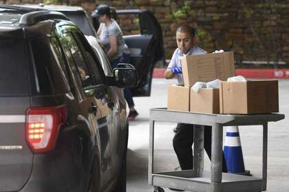 Joe Vidales pulls a cart loaded with groceries and meals to load into an employee's vehicle at USAA's headquarters in March. USAA partnered with Sodexo to offer curbside meal and grocery pickup for employees at its campuses.