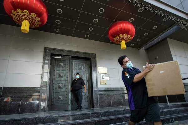 A delivery driver carries a box from the Consulate General of China Thursday, July 23, 2020, in Houston.
