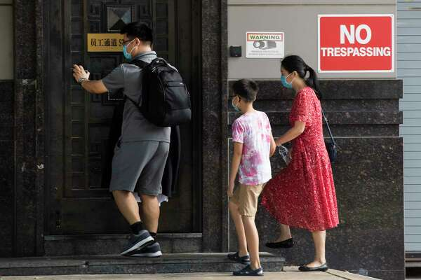 People walk into staff entrance of the Consulate General of China Thursday, July 23, 2020, in Houston.