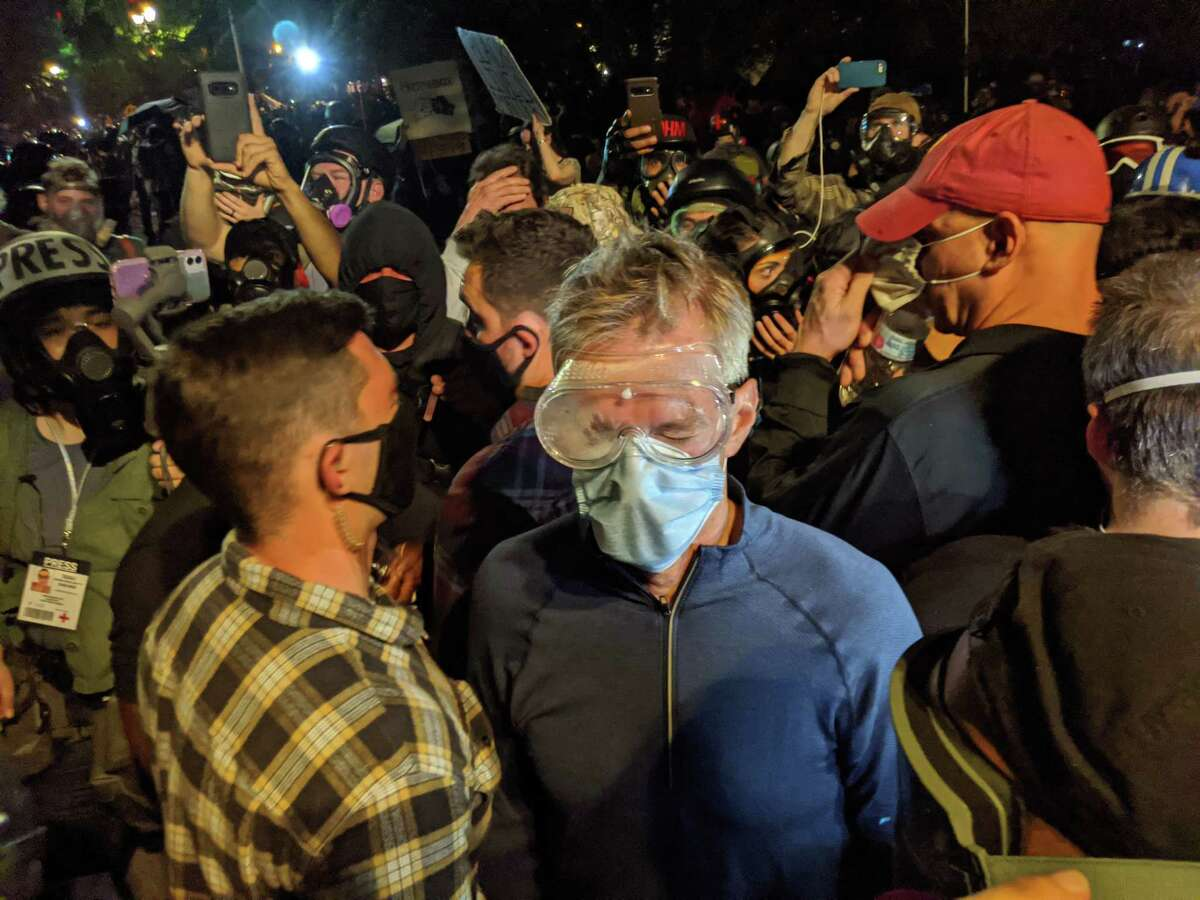 Portland Mayor Ted Wheeler wears goggles and a face mask during a protest against racial inequality and police violence in Portland, Ore. late Wednesday, July 22, 2020. Wheeler, was left coughing and wincing in the middle of his own city Wednesday night after federal officers deployed tear gas into a crowd of protesters that he had joined outside the federal courthouse. (Mike Baker/The New York Times)