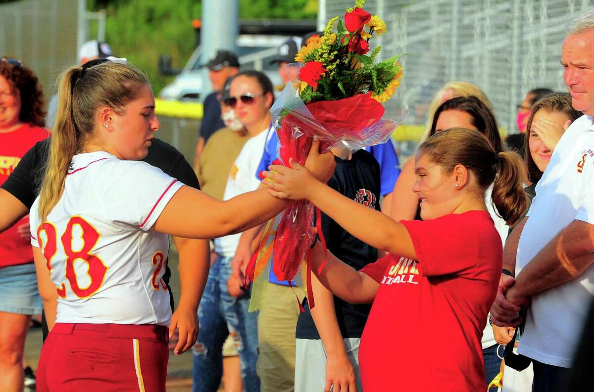 Saint Joseph's Hannah Fahey, left, hands a bouquet of flowers she received to her sister Cara before the start of softball action between the Brakettes and state high school all-stars in an exhibition game at DeLuca Field in Stratford, Conn., on Thursday July 23, 2020. Fahey and the other all-stars were honored before the game in celebration of the colleges each will attend. Fahey will be attending Auburn University in Alabama.
