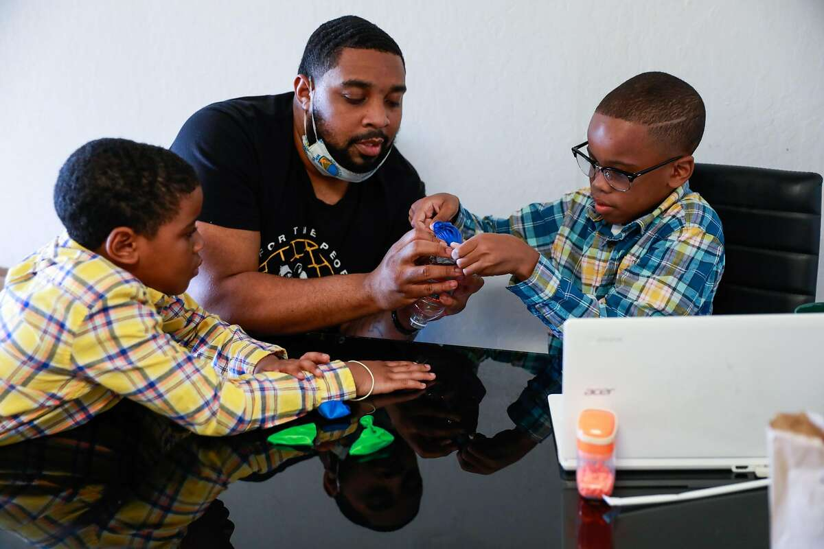 James Thomas helps his son Jamal Lee Jr., 10, re-create a lung with a balloon and plastic bottle during an online science class at their San Leandro home as his other son, Javaughn Thomas, 7, watches.