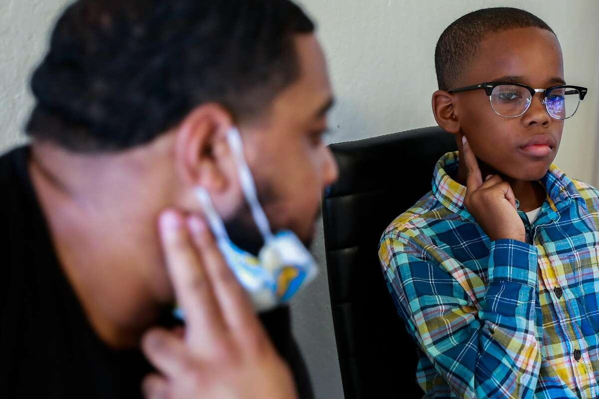 James Thomas and son Jamal Lee Jr. check their pulse as Jamal learns about the heartbeat during an online science class.