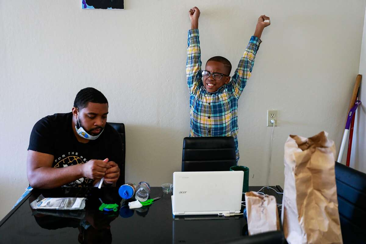 James Thomas (left) sits with his son Jamal Lee Jr., who took a big stretch after completing an online science class.