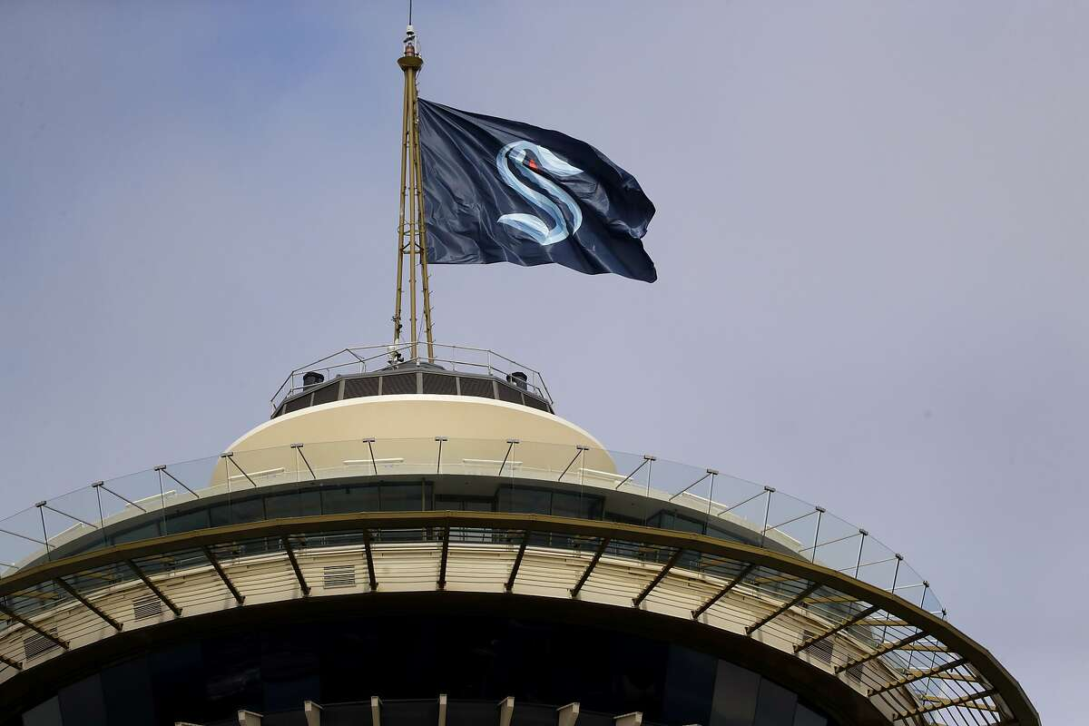 A flag with the new logo for the newly-named Seattle NHL team, the Seattle Kraken, flies atop the iconic Space Needle Thursday, July 23, 2020, in Seattle. The hockey expansion franchise unveiled its nickname Thursday, ending 19 months of speculation about whether the team might lean traditional or go eccentric with the name for the league's 32nd team. Seattle's colors are a deep dark blue with a lighter shade of blue as a complement. (AP Photo/Elaine Thompson)