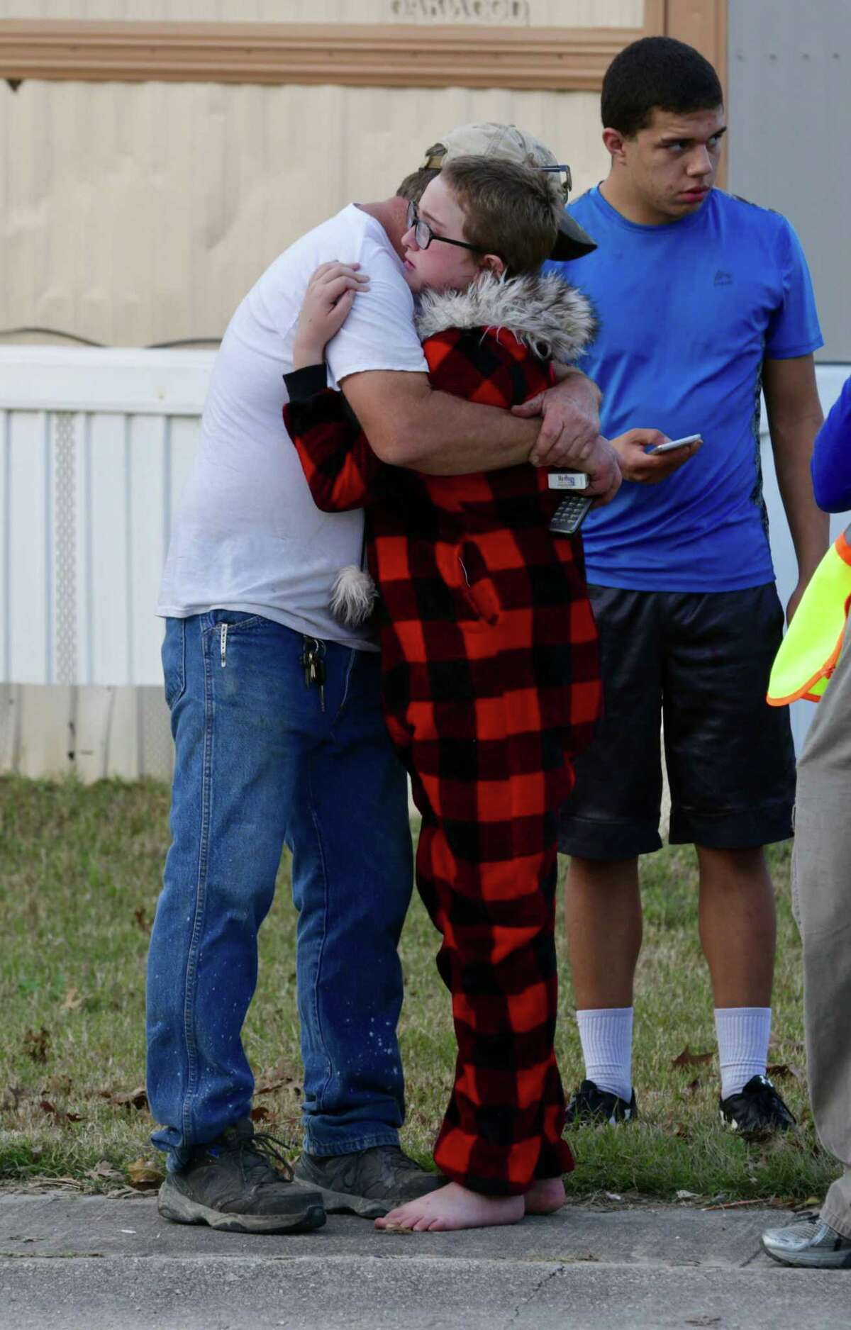 Ron Lawrence, left, comforts his daughter, Kallie Lawrence, 11, who knew Kameron Prescott, a 6-year-old boy who was fatally wounded by Bexar County Sheriff's deputies while they were pursuing a suspect in the Pecan Grove mobile home community in Schertz on Dec. 21, 2017.
