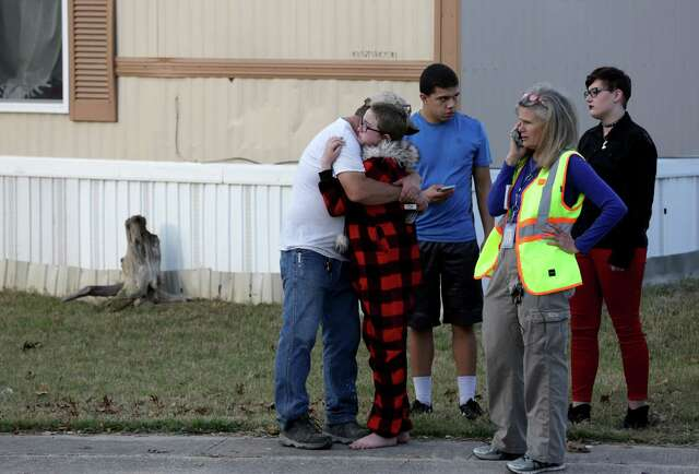 Ron Lawrence, left, comforts his daughter, Kallie Lawrence, 11, who knew Kameron Prescott, a 6-year-old boy who was shot by Bexar County Sheriff's deputies while they were pursuing a suspect in the Pecan Grove mobile home park in Schertz on Dec. 21, 2017.