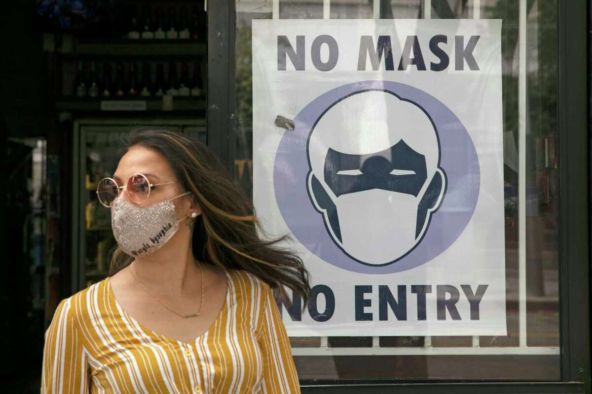 FILE - A woman walks out of a liquor store past a sign requesting its customers to wear a mask Tuesday, June 23, 2020, in Santa Monica, Calif. (AP Photo/Jae C. Hong, File)