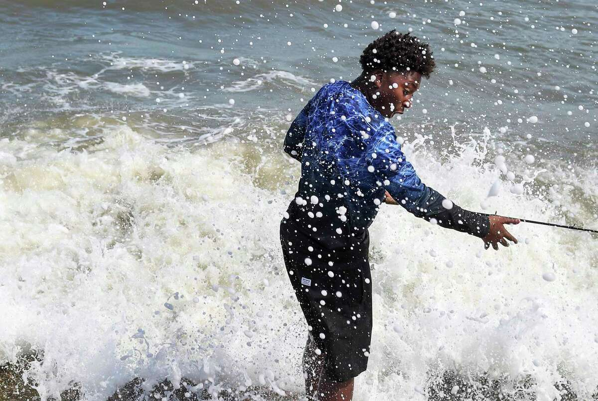 """Jaden Simmons, 14, reacts as he is hit by a wave while fishing at the end of a jetty Thursday, July 23, 2020, at the beach in Galveston. """"I hope the big one doesn't come,"""" he said shortly before."""