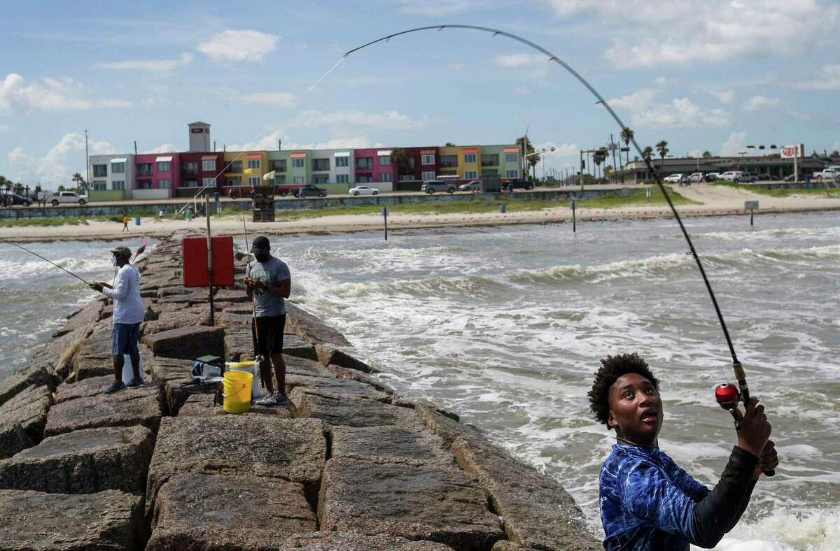 Jaden Simmons, right, 14, casts his line into the sea as he fishes with his father, Riley Simmons, center, and his great-uncle Orthell Rivers, left, on Thursday, July 23, 2020, at the beach in Galveston.