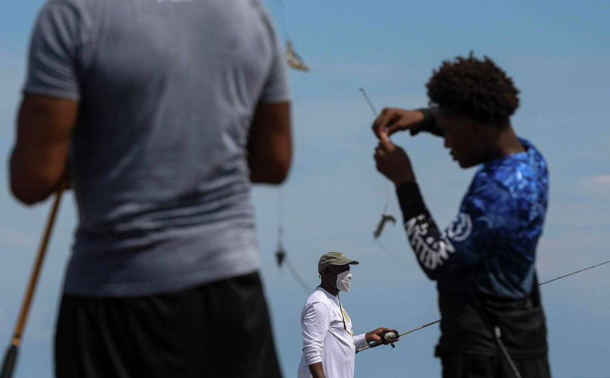 Orthell Rivers, center, fishes with his nephew Riley Simmons, left, and Simmons' son Jaden Simmons, 14, on a jetty Thursday, July 23, 2020, at the beach in Galveston.