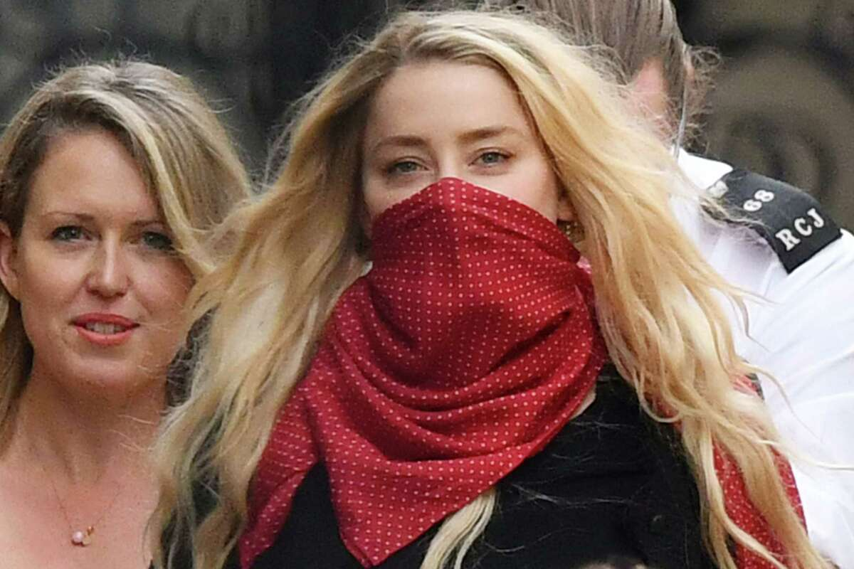 US actress Amber Heard (red face covering) leaves on day thirteen of the libel trial by her former husband US actor Johnny Depp against News Group Newspapers (NGN), at the High Court in London, on July 23, 2020. - US actress Amber Heard on July 23 said her ex-husband Johnny Depp threw dozens of bottles at her
