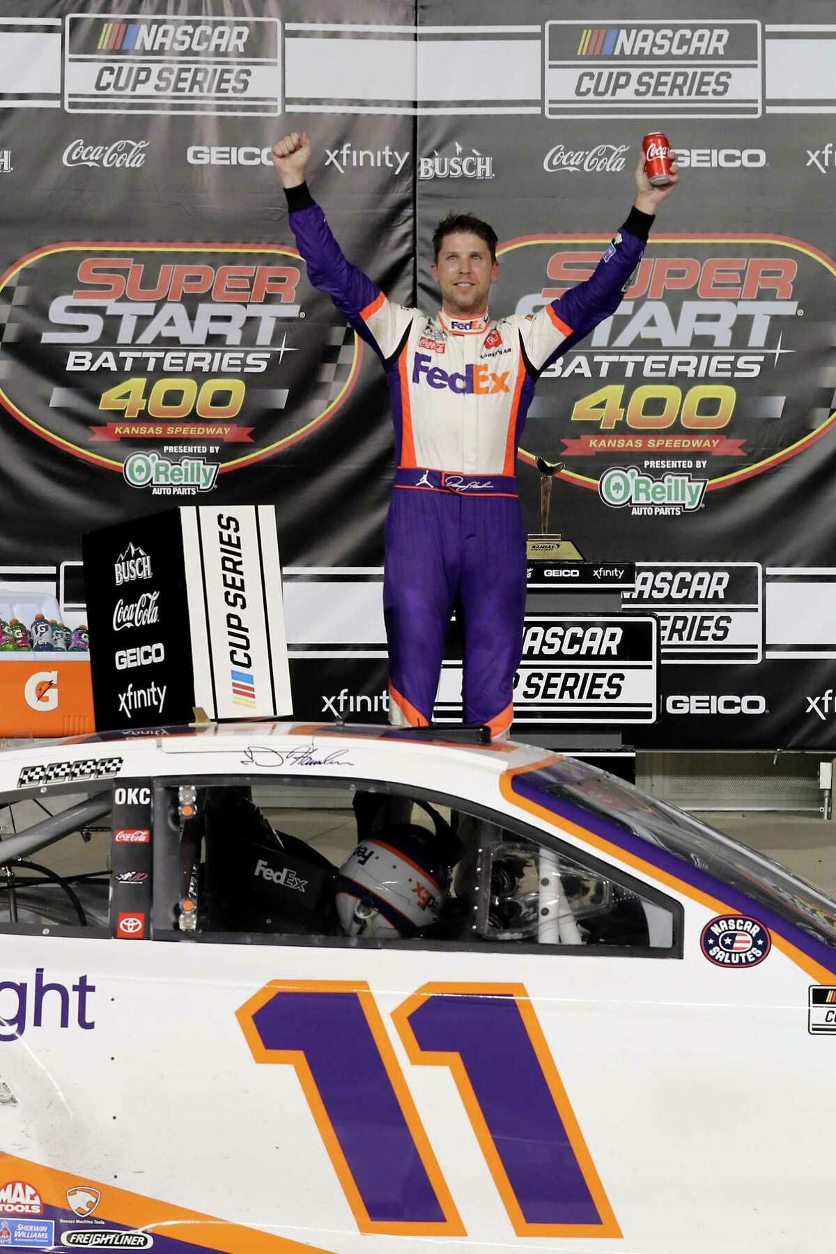 KANSAS CITY, KANSAS - JULY 23: Denny Hamlin, driver of the #11 FedEx Office Toyota, celebrates in Victory Lane after winning the NASCAR Cup Series Super Start Batteries 400 Presented by O'Reilly Auto Parts at Kansas Speedway on July 23, 2020 in Kansas City, Kansas. (Photo by Jamie Squire/Getty Images)