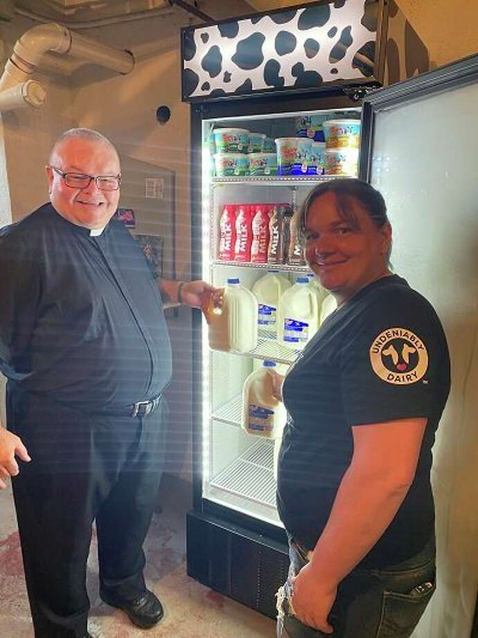 Fr. T.J. Fleming, pastor of St. Hubert Parish and Missy Siemen put milk in the cooler that was awarded to the parish food pantry after being nominated by Missy. (Submitted Photo)