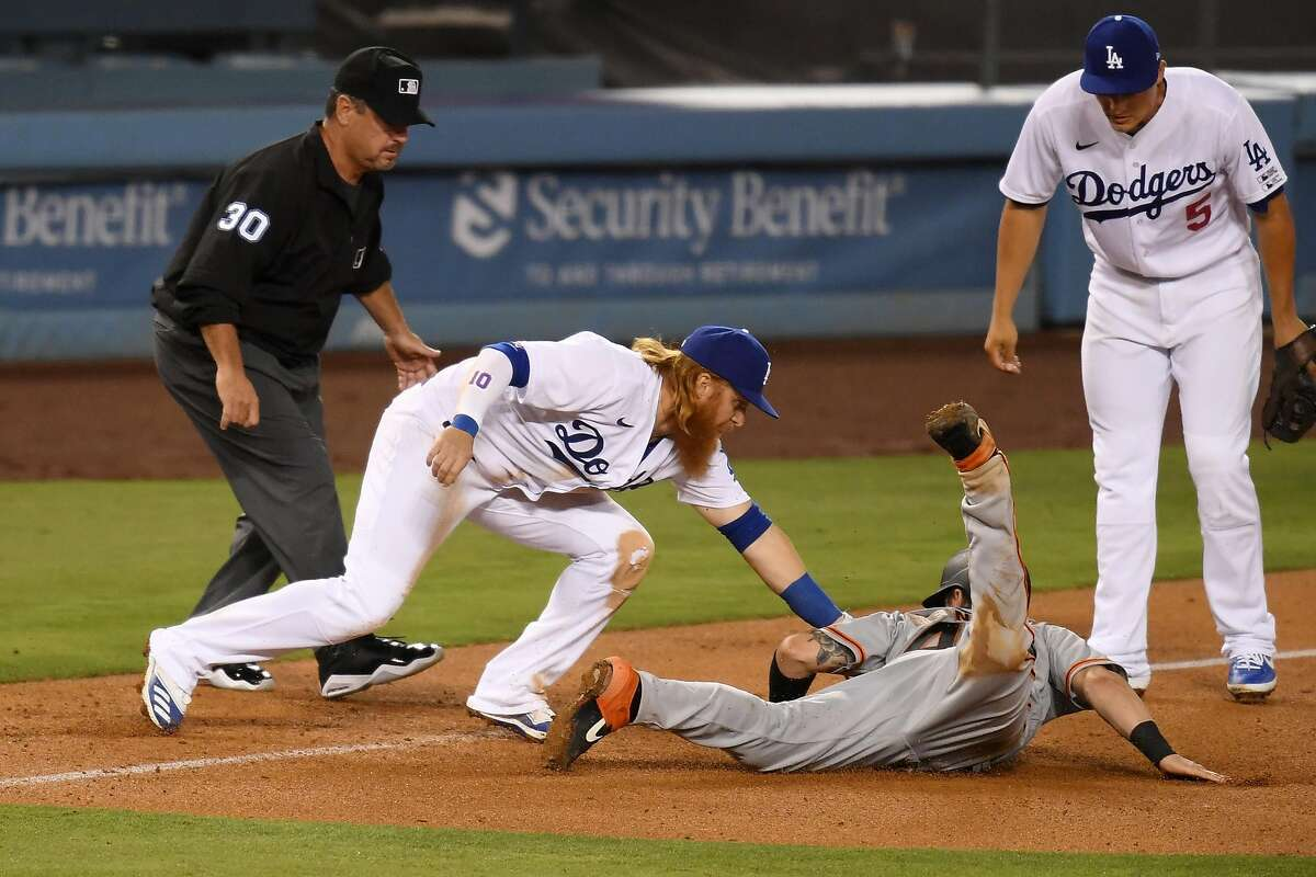 LOS ANGELES, CALIFORNIA - JULY 23: Justin Turner #10 of the Los Angeles Dodgers tags out Tyler Heineman #43 of the San Francisco Giants at third base during the fifth inning in the Opening Day game at Dodger Stadium on July 23, 2020 in Los Angeles, California. The 2020 season had been postponed since March due to the COVID-19 pandemic. (Photo by Harry How/Getty Images)