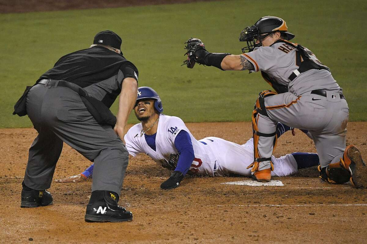 Los Angeles Dodgers' Mookie Betts, center, scores on a fielder's choice hit by Justin Turner as San Francisco Giants catcher Tyler Heineman takes a late throw and home plate umpire Bill Miller makes the call during the seventh inning of an opening day baseball game, Thursday, July 23, 2020, in Los Angeles. (AP Photo/Mark J. Terrill)