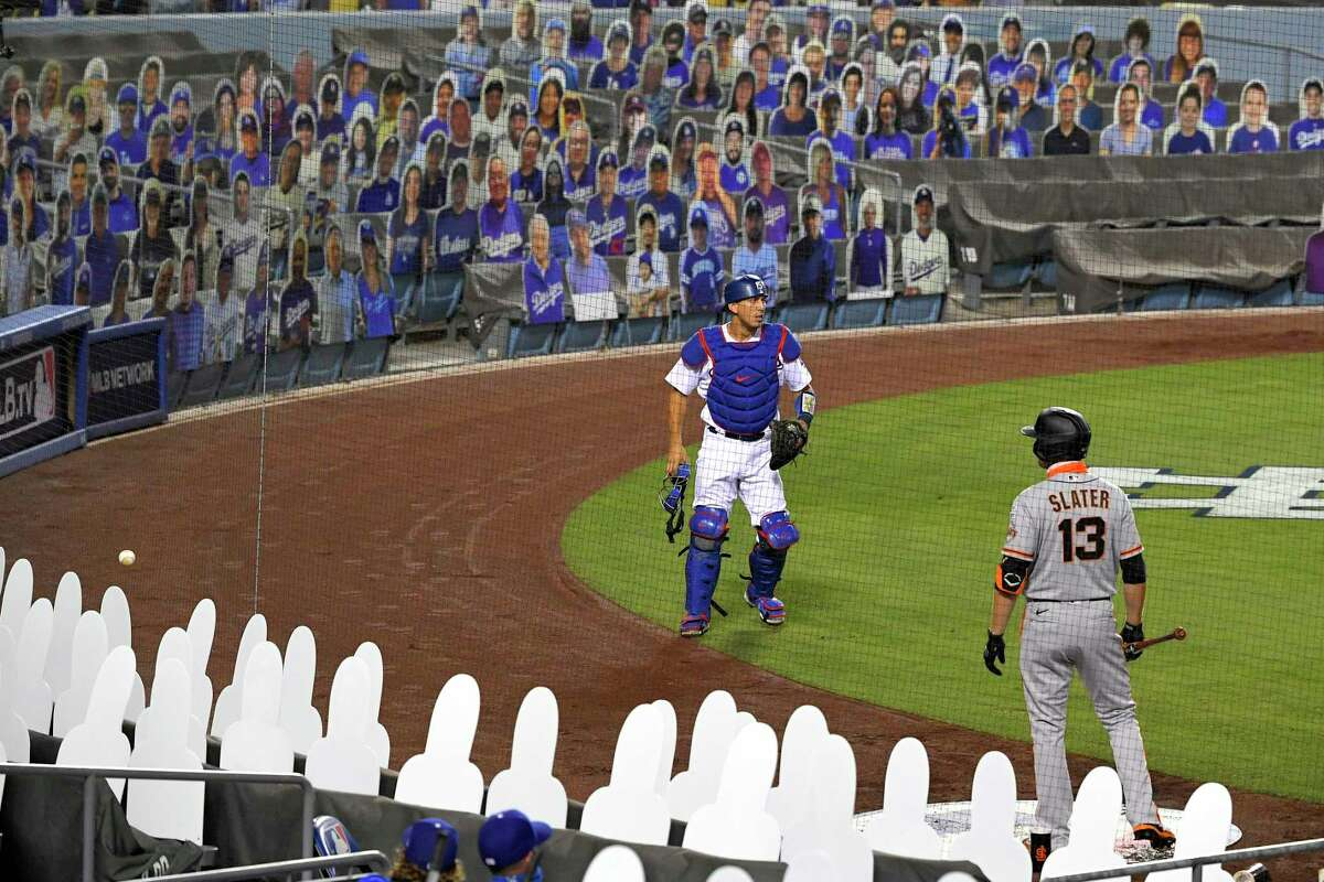 Los Angeles Dodgers catcher Austin Barnes, left, gives up on a foul ball as San Francisco Giants' Austin Slater waits in the on-deck circle during the fifth inning of an opening day baseball game, Thursday, July 23, 2020, in Los Angeles.