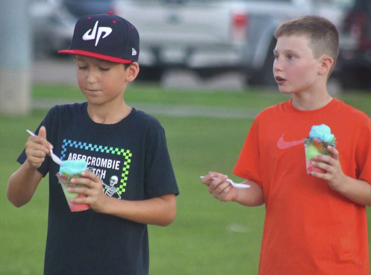 Decker Miller (left) and Mason Wagnon enjoy the cool treat of Italian ice and its many flavors Thursday night that has been on sale at the ballfields this summer.