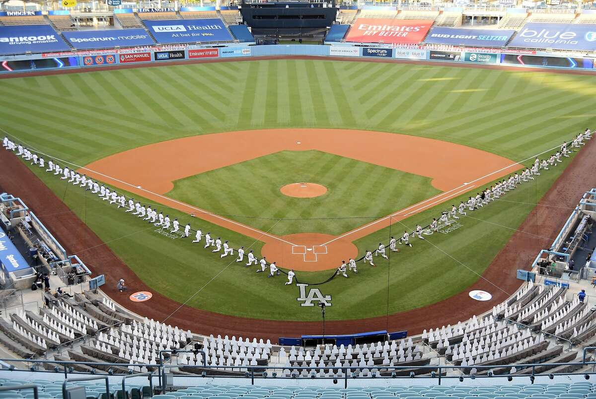 LOS ANGELES, CALIFORNIA - JULY 23: Members of the Los Angeles Dodgers and the San Francisco Giants kneel prior to the national anthem before their game at Dodger Stadium on July 23, 2020 in Los Angeles, California. The 2020 season had been postponed since March due to the COVID-19 pandemic. (Photo by Harry How/Getty Images) *** BESTPIX ***