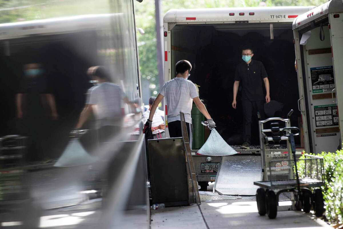 Consulate workers remove items from the Consulate General of China Friday, July 24, 2020, in Houston. U.S.government has ordered the Houston consulate to close by Friday.
