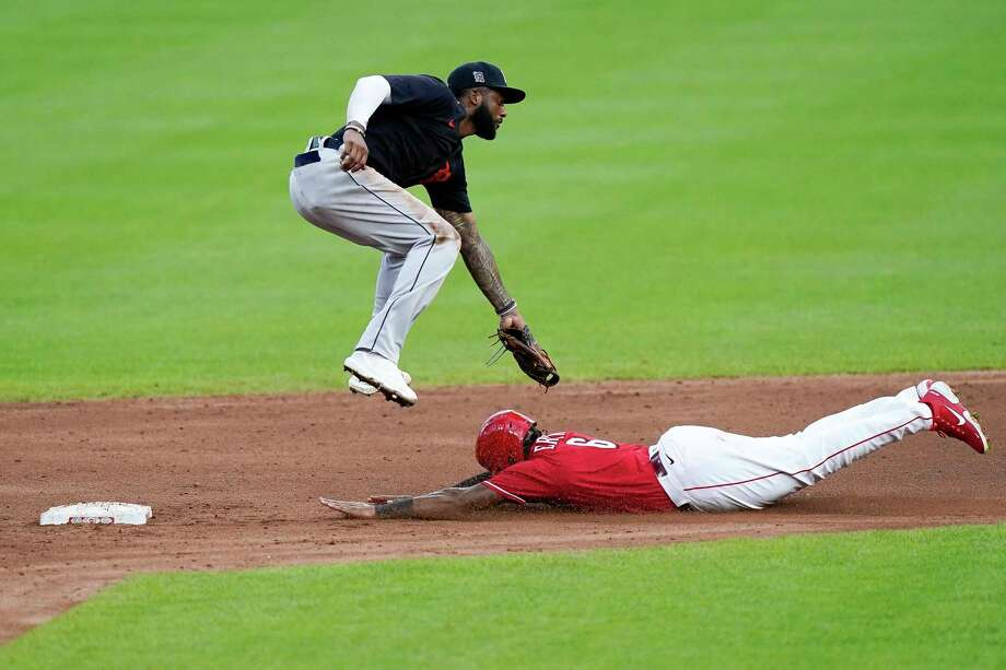 Cincinnati right fielder Phillip Ervin (6) slides safely under the tag of Detroit shortstop Niko Goodrum during the fourth inning of their exhibition baseball game Wednesday at Great American Ballpark in Cincinnati (AP Photo/Bryan Woolston) / Copyright 2020 The Associated Press. All rights reserved.